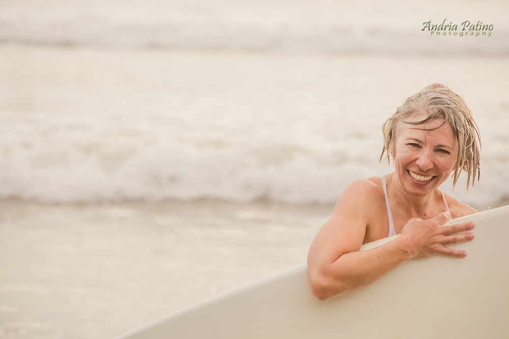 Woman holding surf board and smiling at camera, Santa Teresa, Costa Rica