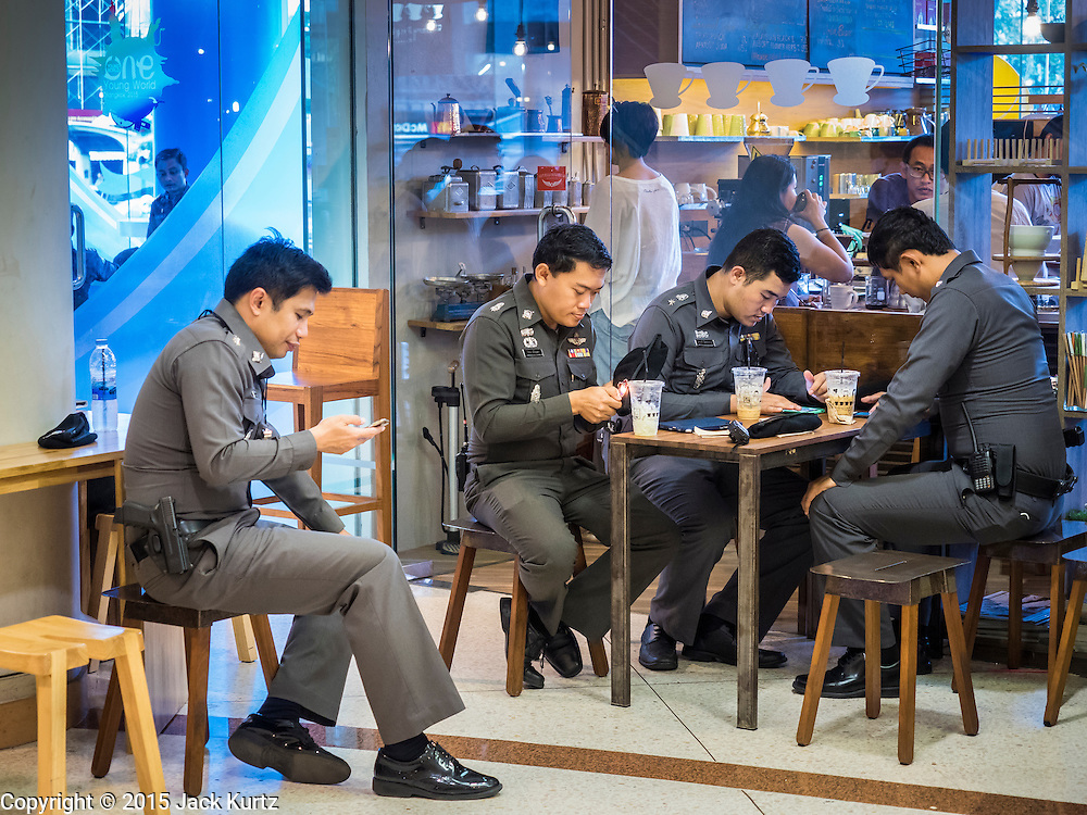 22 MAY 2015 - BANGKOK, THAILAND:  Thai police relax at a coffee shop before confronting protestors at the Bangkok Art and Culture Centre. The Thai military seized power in a coup on May 22, 2014. There were small protests throughout Bangkok Friday to mark the first anniversary of the coup. Police arrested protestors at several locations. The most serious protest was at Bangkok Art and Culture Centre (BACC) where about 100 protestors, mostly students, faced off against police for several hours. Police made numerous arrests at the BACC protest.     PHOTO BY JACK KURTZ