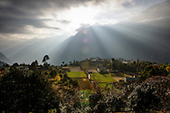 The sun bursts from behind clouds, above the Himalayas, Nepal.
