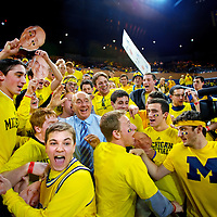 ANN ARBOR, MICHIGAN -- February 5, 2013 -- University of Michigan fans swallow up ESPN sportscaster Dick Vitale as they prepare to take on rival Ohio State University in Ann Arbor, Michigan.  The Wolverines won 76-74 in overtime.   (PHOTO / CHIP LITHERLAND)