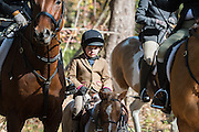 A young rider is lost between her parents horses during the first hunt of the season at Middleton Place Plantation November 27, 2016 in Charleston, SC. Fox hunting in Charleston is a drag hunt using a scented cloth to simulate a fox and no animals are injured.