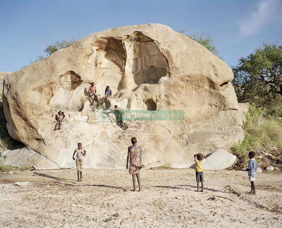 October 3, 2018 - Lake Eyasi, Ngorongoro district, Tanzania - Young Hadza boys climb a huge stone rock next to their camp.The Hadza are one of the last remaining societies, which remain in the world, that survive purely from hunting and gathering. Very little has changed in the way the Hadza live their lives. But it has become increasingly harder for them to pursue the Hadza way of life. Either the Hadza will find a way to secure their land-rights to have access to unpolluted water springs and wild animals, or the Hadzabe lifestyle will disappear, with the majority of them ending up as poor and uneducated individuals within a Westernized society that is completely foreign to them. The hunter gatherer Hadza way of live is under threat. (Credit Image: © Stefan Kleinowitz/ZUMA Wire)