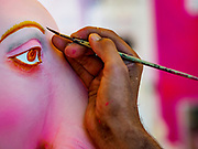 10 SETEMBER 2018 - BANGKOK, THAILAND: A craftsman paints Ganesh statues at Wat Witsanu Hindu Temple (also called the Vishnu Temple) for use in Ganesh Chaturthi observances in Thailand. Indian craftsmen are making statues of the Hindu deity Ganesha for the Ganesh Chaturthi, or Ganesh Festival, held at Hindu temples in September. All of the craftsmen, and the clay they use to fashion the statues, come from India every year to make the statues. Although Thais are predominantly Buddhist, the Lord Ganesh, the Hindu overcomer of obstacles, is worshipped by many Thais and Ganesh Chaturthi is celebrated in many Thai communities.       PHOTO BY JACK KURTZ