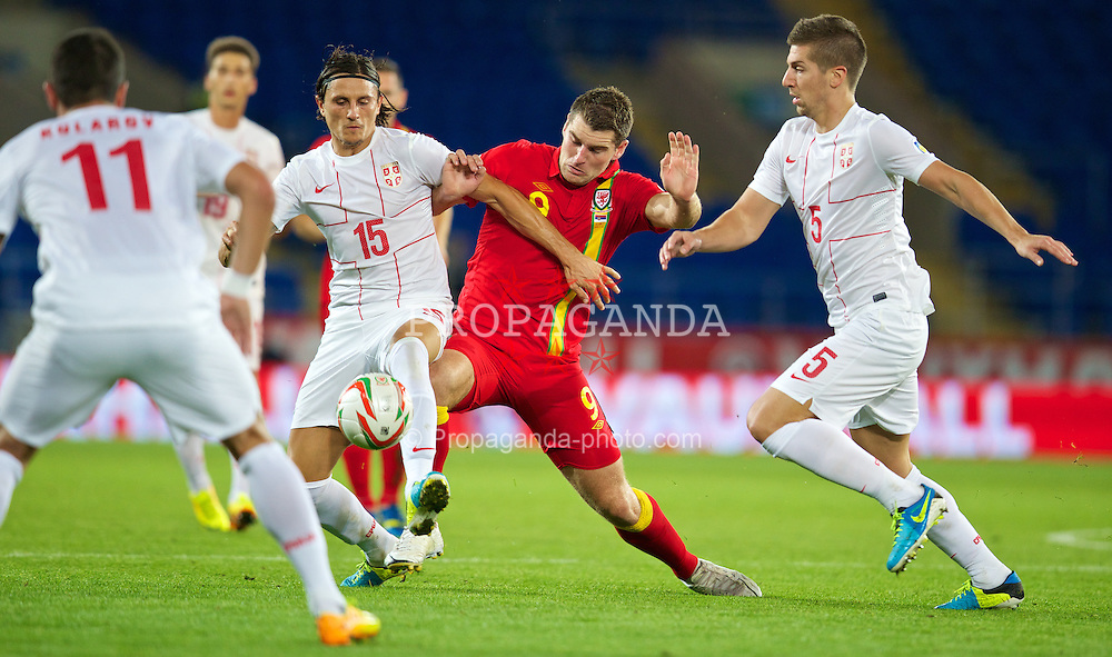 CARDIFF, WALES - Tuesday, September 10, 2013: Wales' Sam Vokes in action against Serbia's Dejan Lekic during the 2014 FIFA World Cup Brazil Qualifying Group A match at the Cardiff CIty Stadium. (Pic by David Rawcliffe/Propaganda)