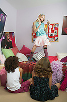 Girl standing on bed singing friends watching from floor