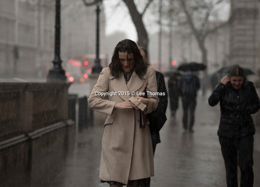 Whitehall, London, UK. 8th December, 2015. Not a happy bunny. Not even Government Cabinet ministers are immune from the heavy rainfall effecting the UK at the moment. Secretary of State for Northern Ireland, Theresa Villiers, gets caught out in a torrential downpour on her way to the weekly cabinet meeting at Downing Street. Whilst the majority of ministers were ushered into Number 10 in luxury vehicles Mrs Villiers decided to walk much to her dismay. // Lee Thomas, Flat 47a Park East Building, Bow Quarter, London, E3 2UT. Tel. 07784142973. Email: leepthomas@gmail.com. www.leept.co.uk (0000635435)