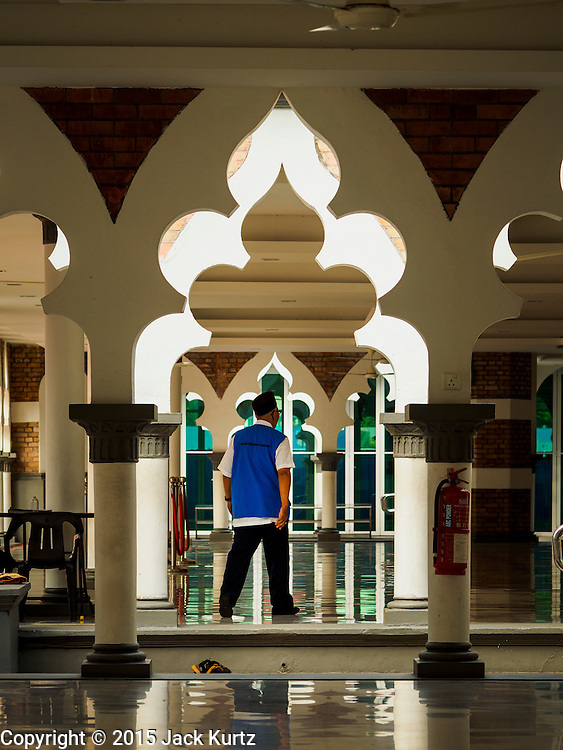 06 JUNE 2015 - KUALA LUMPUR, MALAYSIA: A Malaysian man walks through a prayer area at Masjid Jamek. Built in 1909, Jamek Mosque is one of the oldest mosques in Kuala Lumpur. It is located at the confluence of the Klang and Gombak River and was designed by Arthur Benison Hubback. The mosque was a built in the style of Mughal (northern India) architecture.  Before the national mosque, Masjid Negara, was opened in 1965, Masjid Jamek served as Kuala Lumpur's main mosque.     PHOTO BY JACK KURTZ