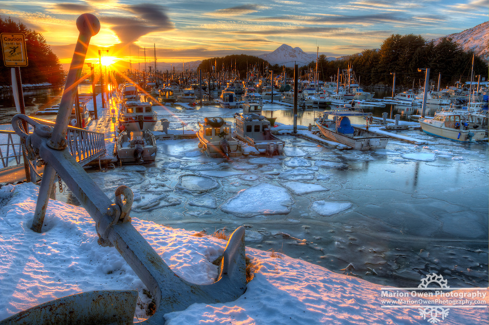 Late afternoon sun sets over boats tied up in Saint Herman Boat Harbor; ice floes clog part of the waterway; a large anchor, resting on snow and ice, dominates left foreground of image, Kodiak, Alaska, Southwest, Winter HDR