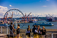 Tourists take in the view of  the Seattle Great Wheel (ferris wheel) with Puget Sound in background, from Pike Place Market, Seattle, Washington USA.