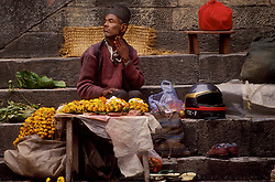 KATHMANDU, NEPAL - OCTOBER 1992 - A street merchant sells his merchandise in Kathmandu, the only sign of modern times is his motorcycle helmet. <br />