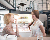 Side view of cheerful young women gossiping in cafe