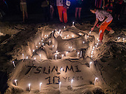 26 DECEMBER 2014 - PATONG, PHUKET, THAILAND: Thai students lights candles for victims of the 2004 tsunami on Patong Beach in Patong, Phuket. Hundreds of people died in Patong and nearly 5400 people died on Thailand's Andaman during the 2004 Indian Ocean Tsunami that was spawned by an undersea earthquake off the Indonesian coast on Dec 26, 2004. In Thailand, many of the dead were tourists from Europe. More than 250,000 people were killed throughout the region, from Thailand to Kenya. There are memorial services across the Thai Andaman coast this weekend.    PHOTO BY JACK KURTZ