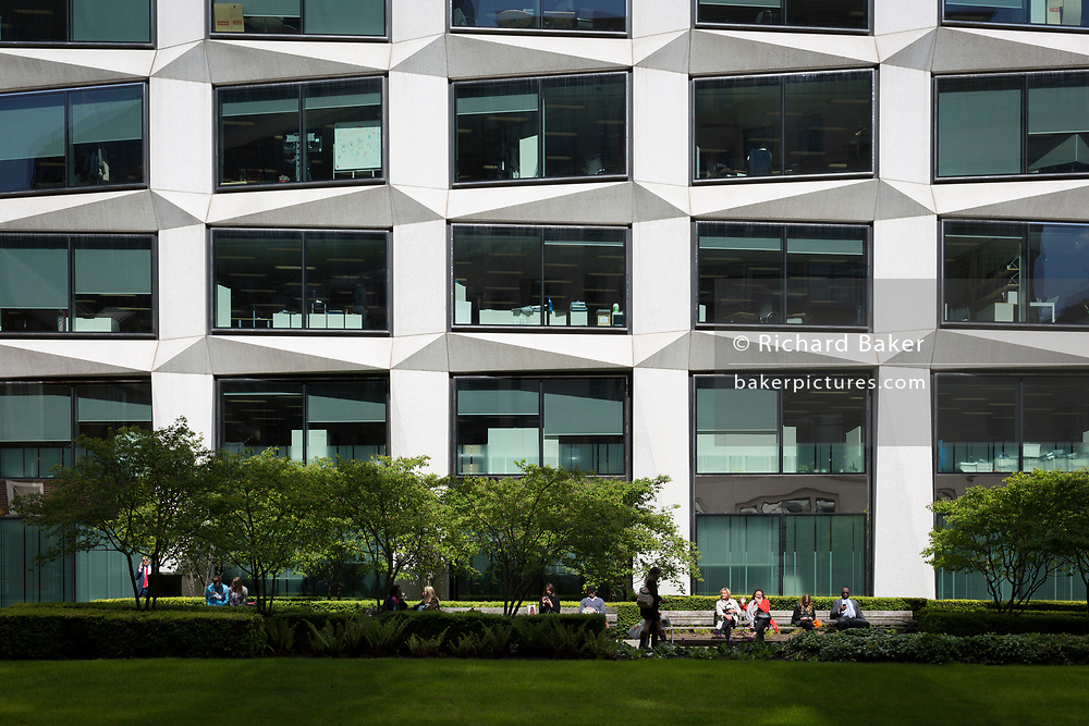 City workers enjoy spring sunshine in a small green space outside corporate offices, on 19th April, in the City of London, England.