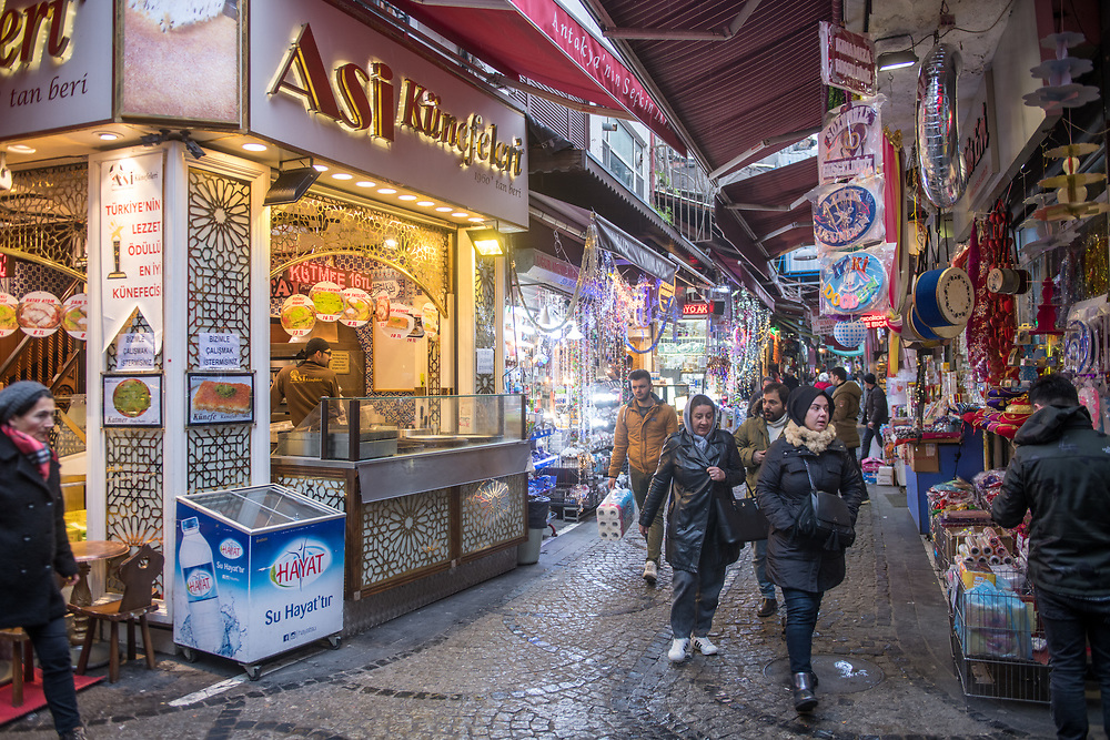 Shoppers walk along narrow street of outdoor market under the coverage of awnings from the stores, Istanbul, Turkey
