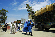 A women wearing a traditional burqa arrives from Afghanistan at the Torkham border post in Peshawar, Pakistan on Monday Aug. 7, 2006. Torkham is the most important border crossing on the northeast transit route between Afghanistan and Pakistan. The Torkham border processes around 1,400 vehicles per day, 79% of which is heavy truck and cargo traffic. Long lines of vehicles and oil tankers can also be seen across the Torkham border between Afghanistan and Pakistan as Afghan officials stop them for fear of terrorism.