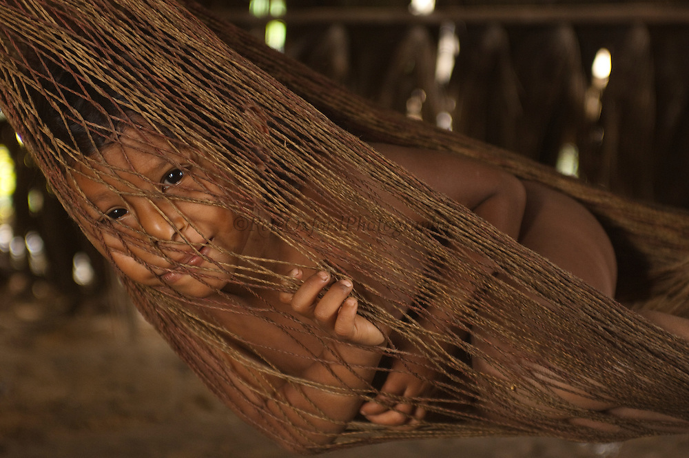 Huaorani Indian child in hammock. Gabaro Community. Yasuni National Park.<br /> Amazon rainforest, ECUADOR.  South America<br /> This Indian tribe were basically uncontacted until 1956 when missionaries from the Summer Institute of Linguistics made contact with them. However there are still some groups from the tribe that remain uncontacted.  They are known as the Tagaeri &amp; Taromenani. Traditionally these Indians were very hostile and killed many people who tried to enter into their territory. Their territory is in the Yasuni National Park which is now also being exploited for oil.
