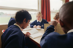 Secondary school pupils sitting around desk in classroom,