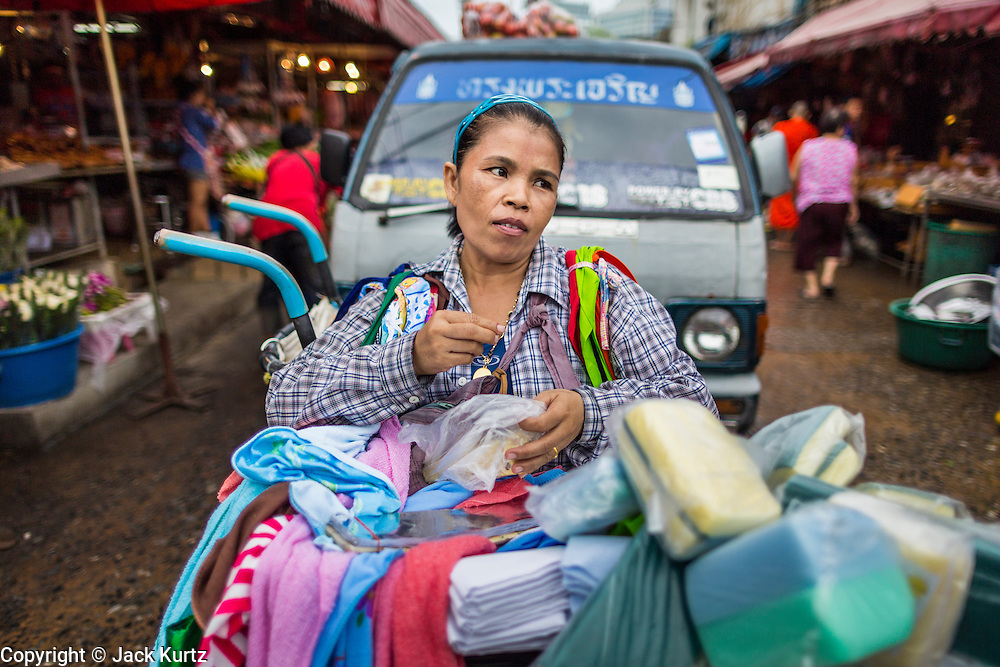 """24 AUGUST 2013 - BANGKOK, THAILAND: A woman selling cleaning supplies waits for customers on a road in Khlong Toei Market in Bangkok. Thailand entered a """"technical"""" recession this month after the economy shrank by 0.3% in the second quarter of the year. The 0.3% contraction in gross domestic product between April and June followed a previous fall of 1.7% during the first quarter of 2013. The contraction is being blamed on a drop in demand for exports, a drop in domestic demand and a loss of consumer confidence. At the same time, the value of the Thai Baht against the US Dollar has dropped significantly, from a high of about 28Baht to $1 in April to 32THB to 1USD in August.     PHOTO BY JACK KURTZ"""