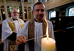 © licensed to London News Pictures. London, UK.  11/09/2011.  Fathers James Roesthal (left) and Natim Nassar (right) light a candle at Grosvenor Chapel near the U.S Embassy today following a service to remember the people who lost their life in the 9/11 terrorist attacks. A service is being held at the 9/11 memorial outside the U.S Embassy in London today (11/09/2011) to mark the 10th anniversary of the attack ono the Twin Towers in New York, in which over 2800 people died. Photo credit: Ben Cawthra/LNP