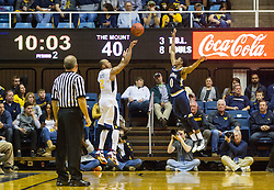Nov 11, 2016; Morgantown, WV, USA; West Virginia Mountaineers guard Jevon Carter (2) shoots a three pointer over Mount St. Mary's Mountaineers guard Junior Robinson (0) during the second half at WVU Coliseum. Mandatory Credit: Ben Queen-USA TODAY Sports