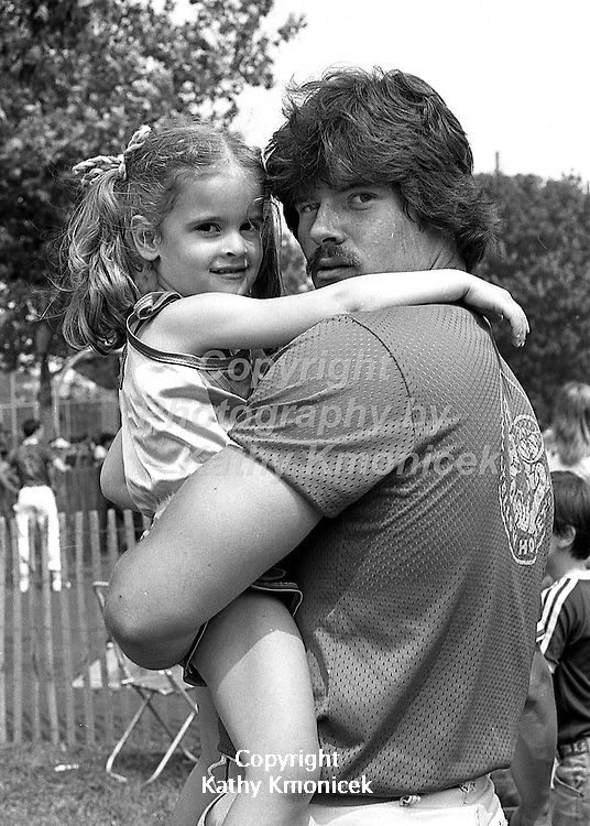 A Hempstead Fire Department Yellow Hornets racing team member and child on the sidelines in 1981.<br />  &copy; Photography by Kathy Kmonicek