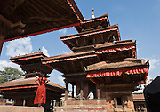 A woman in a red dress studies old wooden pagoda buildings in Kathmandu's Durbar Square (or Palace Square; officially called Hanuman Dhoka). Kathmandu, the largest city in Nepal (700,000 people), is sometimes called Kantipur, a name from the Malla Dynasty. The city stands at an elevation of 6235 feet / 2230 meters.