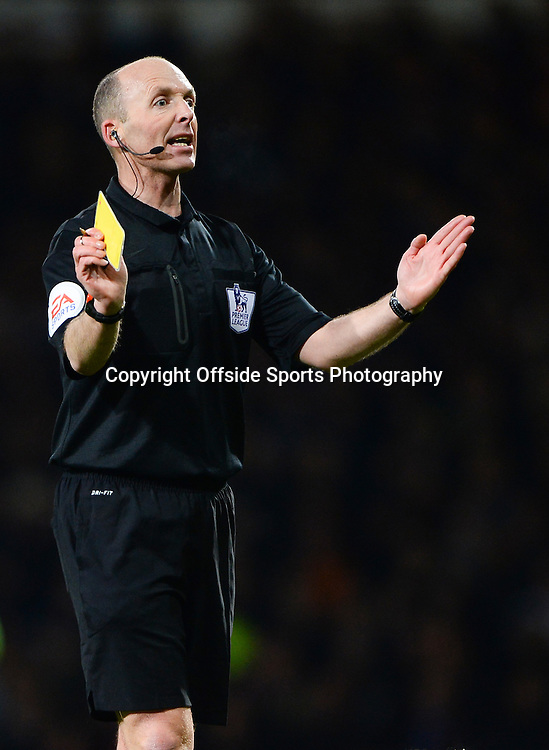 26 March 2014 - Barclays Premier League - West Ham United v Hull City - Referee, Mike Dean shows a yellow card - Photo: Marc Atkins / Offside.