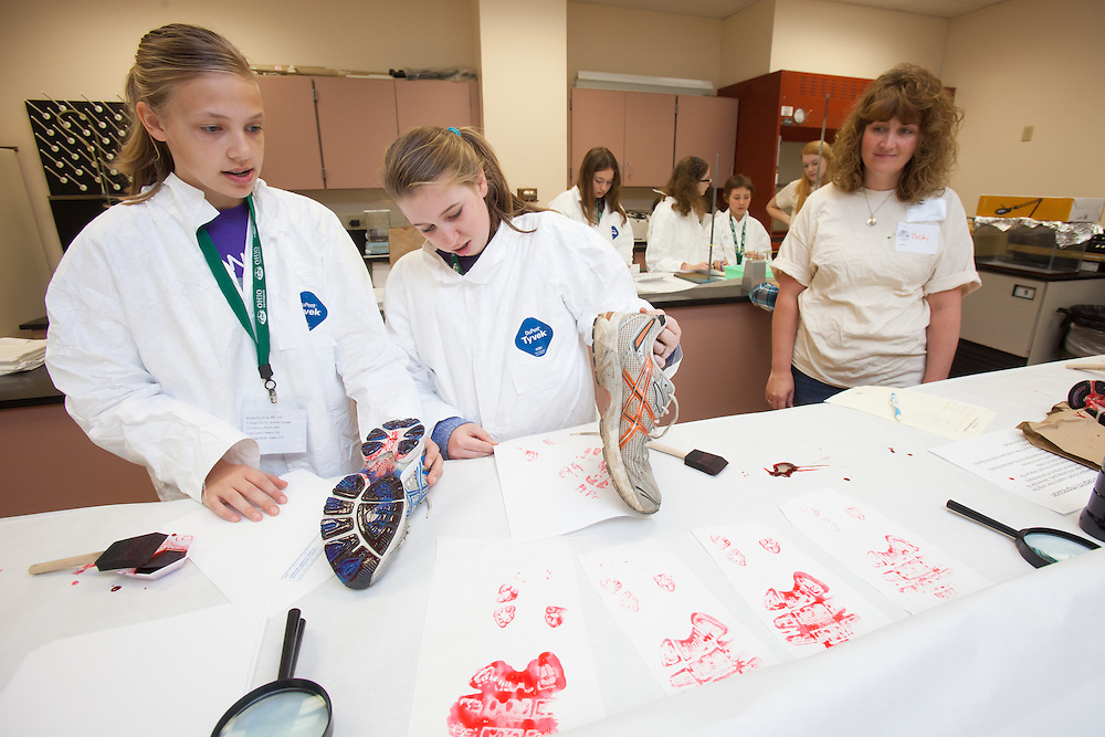 Meredith Coil and  Jordan Mader examine bloody footprints from a mock crime scene during the Tech Savvy workshop CSI Athens at Ohio University May 17, 2014.  The full day event exposes girls from sixth through ninth grade to the field of science, technology, engineering and math.   Photo by Ohio University / Jonathan Adams