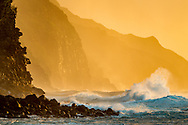 Large unstable ocean waves charge toward cliffs on the rugged Na Pali Coast, with the light of the setting sun, Kauai, Hawaii. © 2010 David A. Ponton