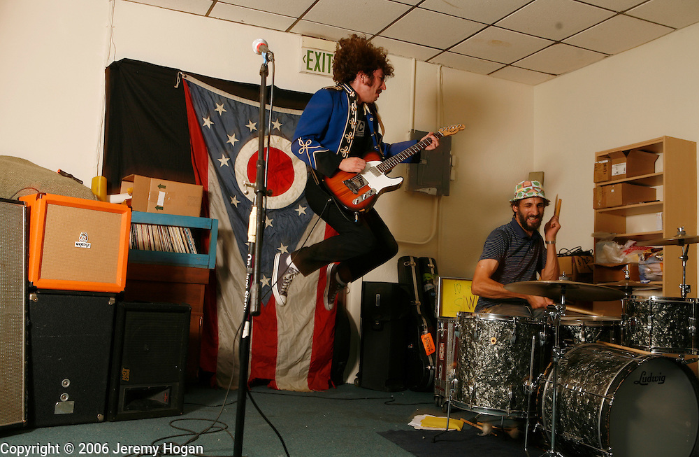 Dave Doughman, of Swearing at Motorists, jumps while he performs at Landlocked Records. Joseph Siwinski plays drums.