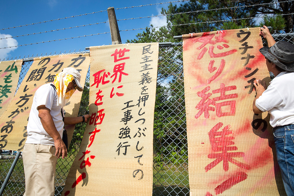 OKINAWA, JAPAN - AUGUST 19 : Anti U.S base protester attaching protest signs in the fence to protest against the construction of helipads in front of the main gate of U.S. military's Northern Training Area in the village of Higashi, Okinawa Prefecture, on August 19, 2016. Japanese government resume construction of total six helipads in a fragile ten million year old Yanbaru forest that is home to endemic endangered species such as the Okinawan rail and Okinawa wood pecker. (Photo by Richard Atrero de Guzman/NURPhoto)