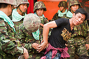 14 MAY 2010 - BANGKOK, THAILAND: A soldier handcuffs a man he arrested during a battle with anti-government protesters on Rama IV Road in Bangkok Friday. Thai troops and anti government protesters clashed on Rama IV Road Friday afternoon in a series of running battles. Troops fired into the air and at protesters after protesters attacked the troops with rocket and small homemade explosives. Unlike similar confrontations in Bangkok, these protesters were not Red Shirts. Most of the protesters were residents of nearby Khlong Toei slum area, Bangkok's largest slum area. The running battle went on for at least two hours.   PHOTO BY JACK KURTZ