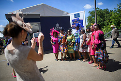 © Licensed to London News Pictures. 21/06/2018. London, UK. A group of Racegoers pose for a photograph at Ladies Day at Royal Ascot at Ascot racecourse in Berkshire, on June 21, 2018. The 5 day showcase event, which is one of the highlights of the racing calendar, has been held at the famous Berkshire course since 1711 and tradition is a hallmark of the meeting. Top hats and tails remain compulsory in parts of the course. Photo credit: Ben Cawthra/LNP