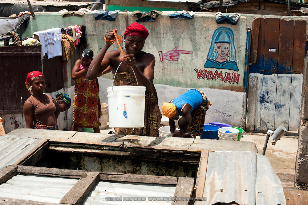 A woman draws water from a privately-owned well in Old Fadama - each bucket of water costs GHC 0.30. With no public water infrastructure, clean water is a major issue and a major expense for residents. Colloquially referred to as 'Sodom and Gomorrah, Old Fadama is located in Ghana's capital Accra and is home to some some 80,000 people.