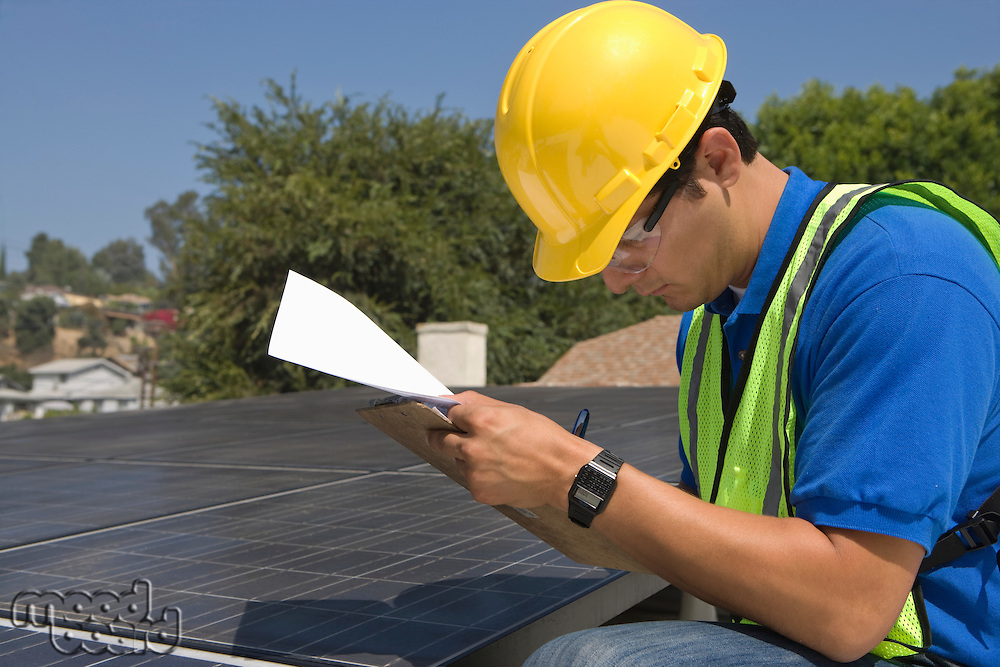 Maintenance worker makes notes with solar array on rooftop Los Angeles California
