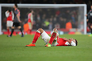 Arsenal midfielder Alex Oxlade-Chamberlain (15) lying on back after final whistle during the Champions League round of 16, game 2 match between Arsenal and Bayern Munich at the Emirates Stadium, London, England on 7 March 2017. Photo by Matthew Redman.