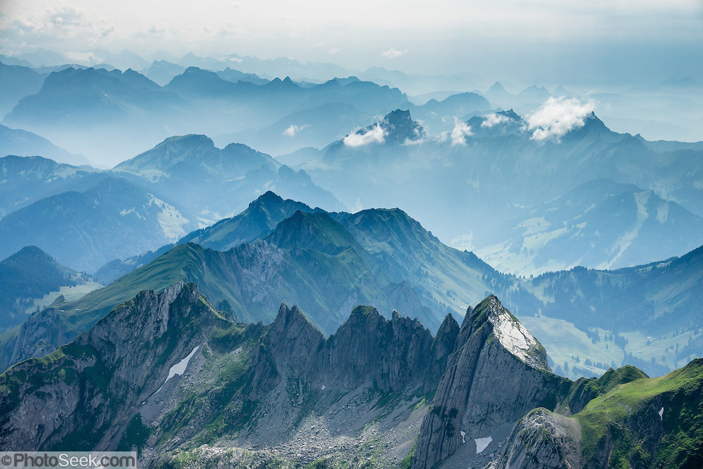 View from atop Säntis (2502 m / 8218 feet), the highest peak of the Alpstein range and the Appenzell Alps, in Switzerland, Europe. Shared by three cantons, Säntis can be reached easily via cable car (Luftseilbahn) from Schwägalp, or with effort via wonderful trails, to see vast mountain views across six countries: Switzerland, Germany, Austria, Liechtenstein, France and Italy. We highly recommend staying overnight on top as we did at Berggasthaus Alter Säntis, a fifth-generation family-run mountain inn since 1850, offering modern private double and dormitory lodging with good food and magnificent views. From where we joined it at Rotsteinpass, the spectacular, rocky Lisengrat trail to Säntis is rigged with safety cables in case of icy or wet conditions (and can be scary for those with fear of heights). In rainy weather the next day, we took the easy aerial tramway down instead of hiking to Ebenalp. The Appenzell Alps rise between Lake Walen and Lake Constance.
