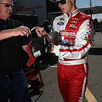 Former Daytona 500 winner and NASCAR Sprint Cup driver Trevor Bayne signs autographs in the garage area, during a NASCAR Daytona 500 practice session at Daytona International Speedway on Wednesday, February 20, 2013 in Daytona Beach, Florida.  (AP Photo/Alex Menendez)