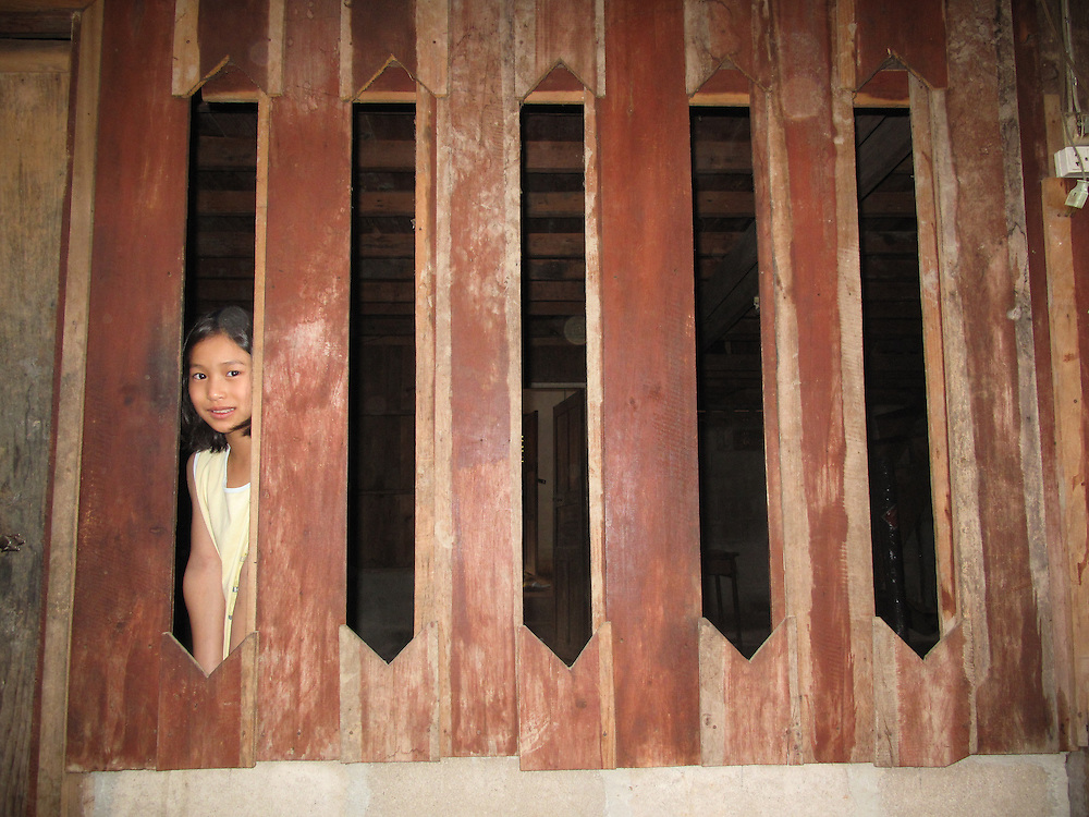 The Little Girl, Thailand by Noon<br /> <br /> Noon comes from a small Christian village. Noon is Thai Karen and recently married. Noon was a teacher at Thonnam School and would love to teach again. She speaks three languages and her English is great. Her favourite colour is orange.<br /> <br /> In this photograph is one of Noon&rsquo;s younger sisters, her name is Chazee. In the Karen language the name means &ldquo;a star that is far away&rdquo;. This photograph was taken in Noon&rsquo;s grandfathers&rsquo; home village, Huay Tong. Noon enjoys the repetition of window shapes and the way her sister is peeking through the window.