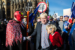 London, UK. 14th February, 2019. Boris Johnson lookalike Drew Galdron, also known as Faux BoJo, holds a Theresa May puppet as he joins anti-Brexit activists, including one dressed as a devil, protesting outside the Houses of Parliament in Westminster.