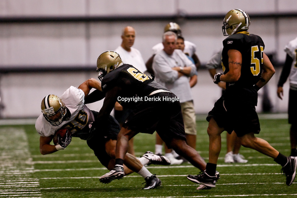 July 31, 2010; Metairie, LA, USA; New Orleans Saints tight end Jimmy Graham (80) is tackled by defensive end Anthony Hargrove (69) during a training camp practice at the New Orleans Saints indoor practice facility. Mandatory Credit: Derick E. Hingle