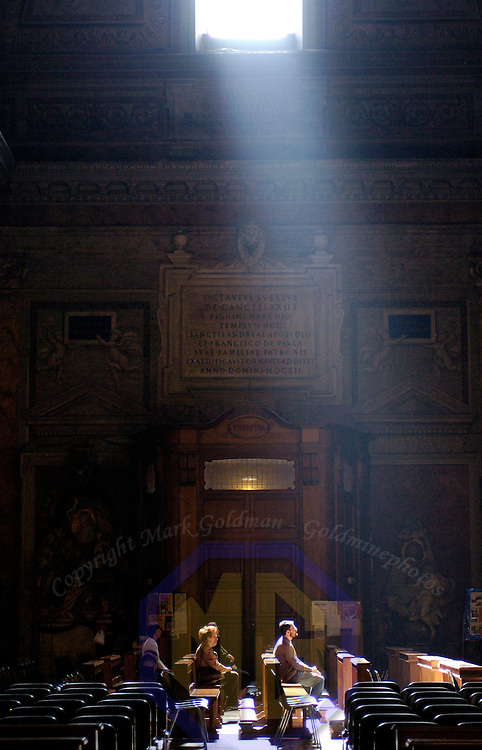 04 May 2004: Afternoon worshipers gather in a very old  church as sunlight pours in from the one opening high on the wall in Rome, Italy on May 4, 2004.