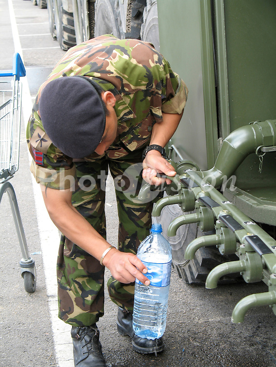 A soldier helping to distribute water from a military tanker  to flood victims in Gloucester, July 2007
