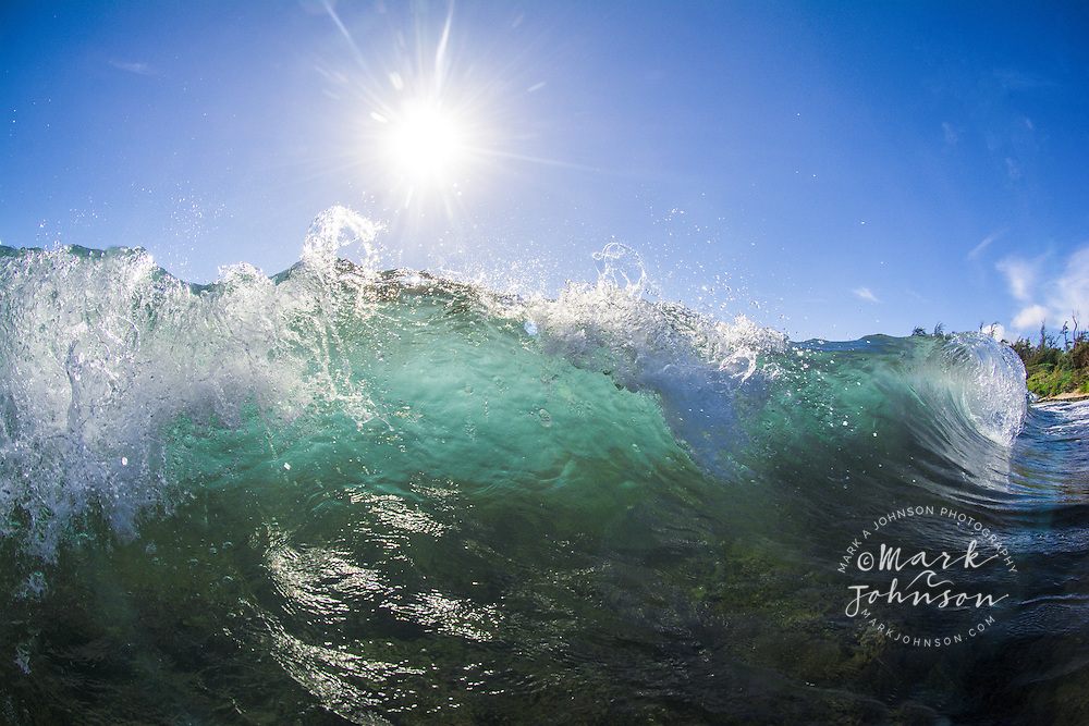 Wave breaking off the beach at Nukolii, Kauai, Hawaii