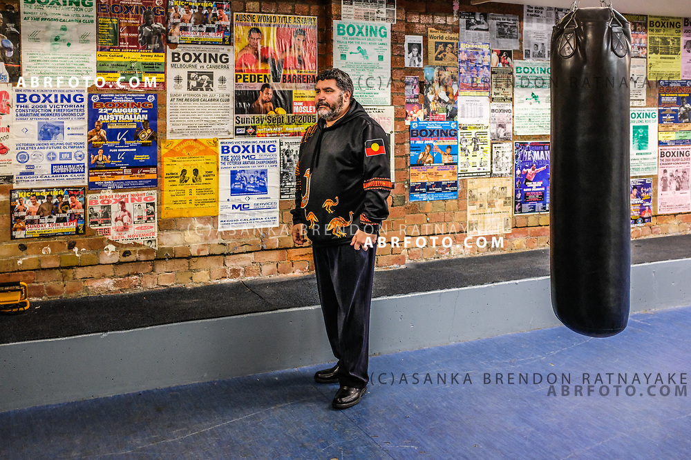 Troy Austin standing in front of Boxing posters of previous fighters who trained at the Aboriginal Youth Sport and Recreation boxing gym on Gertrude Street in Melbourne, Australia, August 30, 2017. The Melbourne Aboriginal Youth Sport and Recreation was started by Troy's father Jock Austin to get Aboriginal youth away from drugs and to provide a safe environment for them to socialise whilst getting healthy. Asanka Brendon Ratnayake for the New York Times