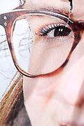 torn page from a newspaper style print with cropped close up of a female eye wearing glasses