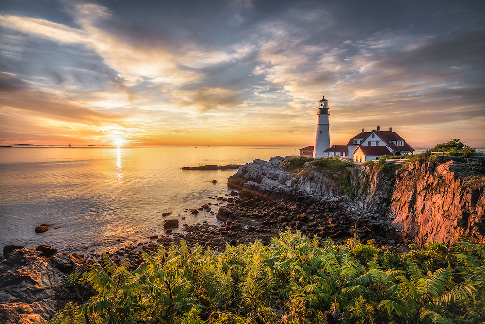 First light shines on the cliffs below Portland Head Light in Cape Elizabeth, Maine.