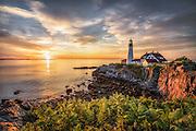 First light shines on the cliffs below Portland Head Light in Cape Elizabeth, Maine.