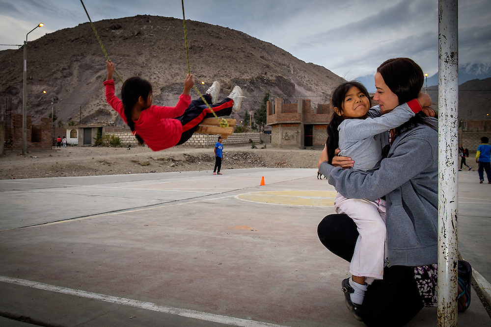 AREQUIPA, PERU - APRIL 7, 2014: Volunteer embracing with student in the community of Flora Tristan for HOOP Peru. HOOP Peru is a NGO fully committed to breaking the cycle of poverty by empowering the Flora Tristan families through enhancing their education.