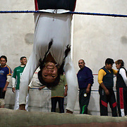 Cholita Yolanda La Amorosa training during a late evening training session with other members of the 'Titans of the Ring' at a makeshift gymnasium in El Alto, Bolivia . The wrestling group performs every Sunday at El Alto's Multifunctional Centre. Bolivia. The group includes the fighting Cholitas, a group of Indigenous Female Lucha Libra wrestlers who fight the men as well as each other for just a few dollars appearance money. El Alto, Bolivia, 28th January 2010. Photo Tim Clayton